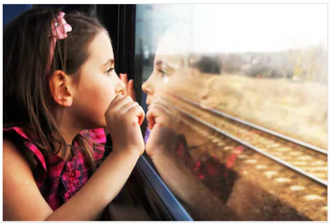 Little girl looking out train window