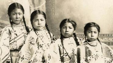 Studio portrait of four unidentified young girls, possibly members of the Crow Indian tribe.