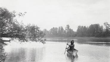 Native American man with canoe on river